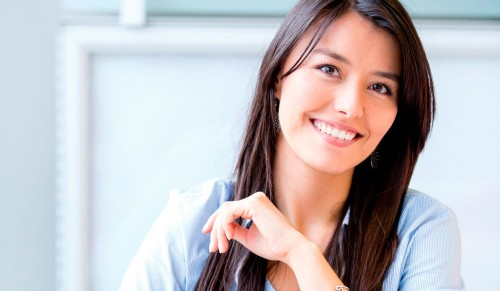A woman sits smiling