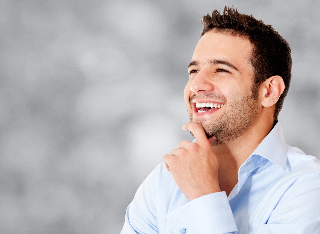 A man smiling and stroking his chin