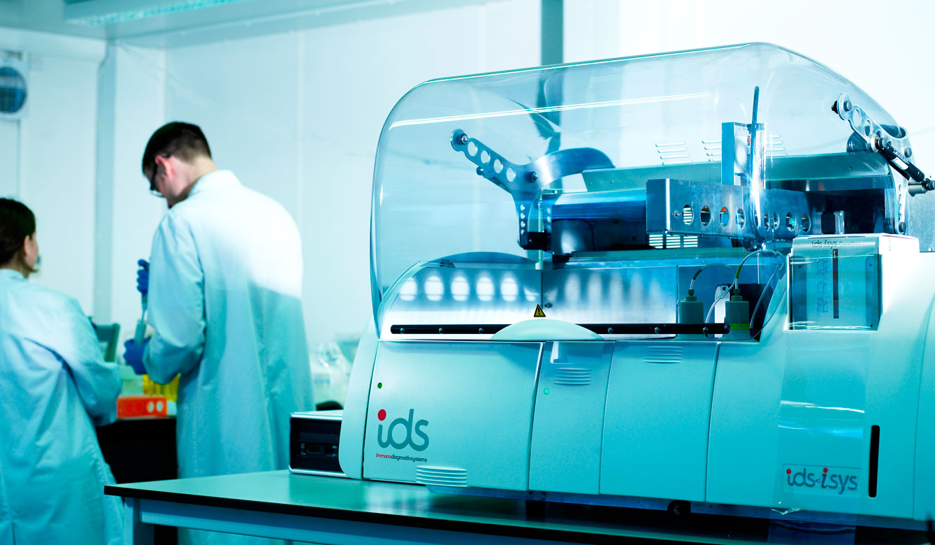 An IDS iSYS machine in the foreground with two technicians in lab coats in the background
