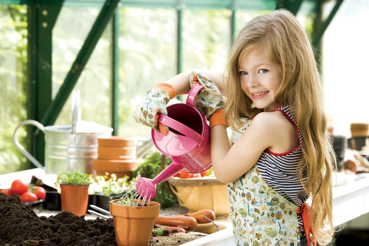 A young girl waters some plants in an indoor greenhouse