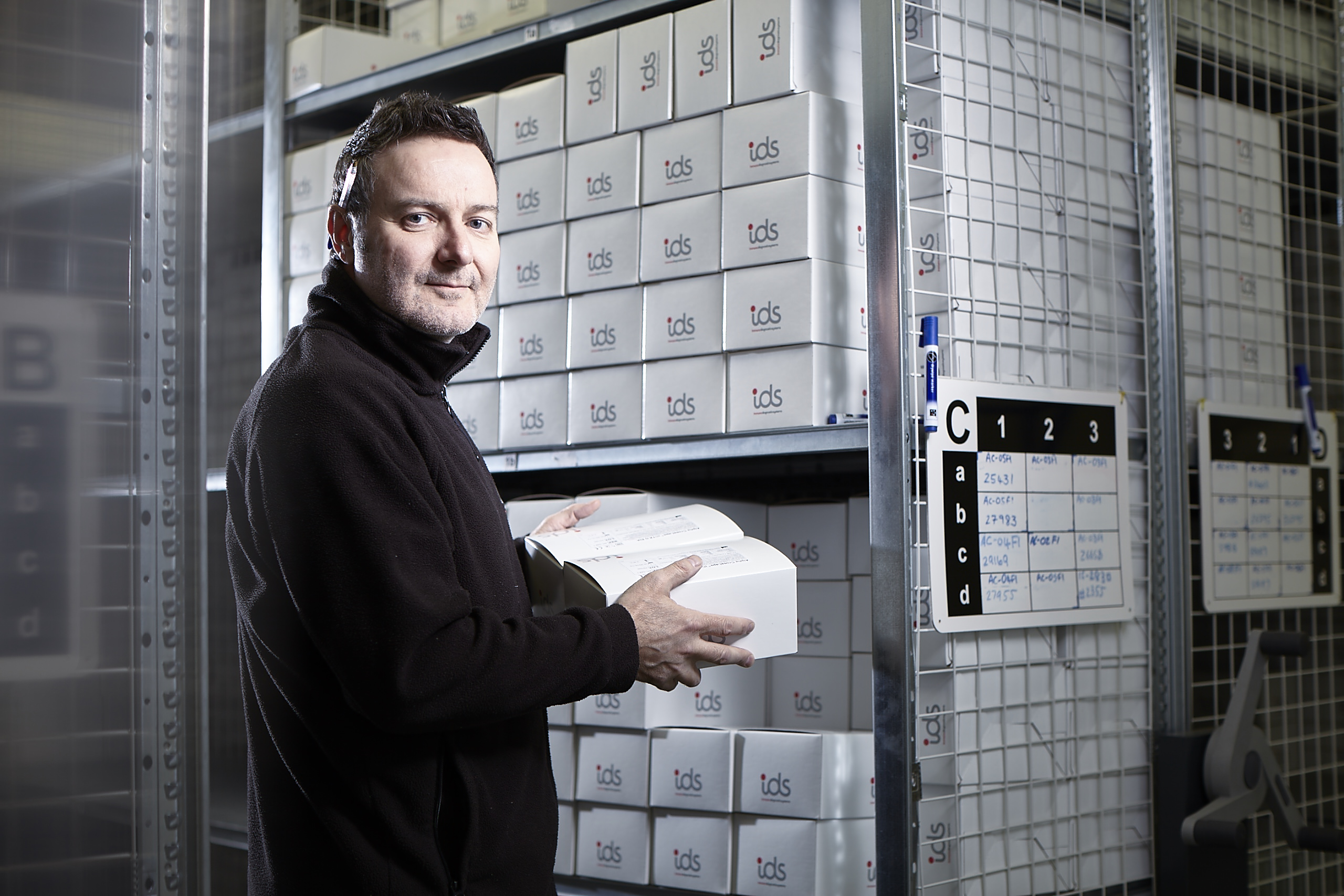 A man loads IDS-branded boxes onto metal shelving