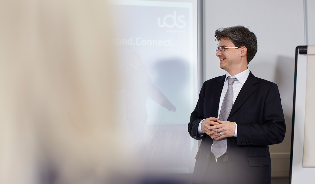 An IDS team member stands in front of a projected screen presenting at the Düsseldorf Fairgrounds in Düsseldorf, Germany.